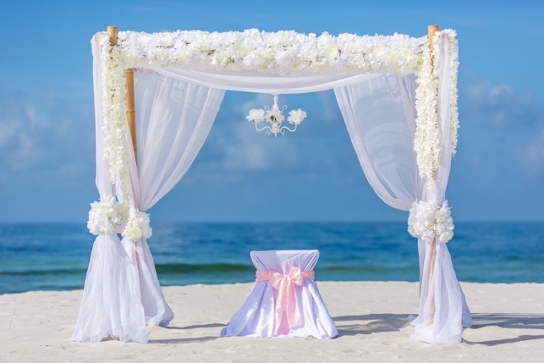 bamboo arbor with flowers and material in panama city beach florida wedding
